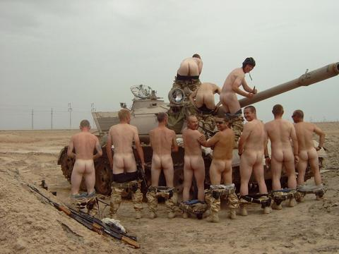 naked soldiers posing on the tank